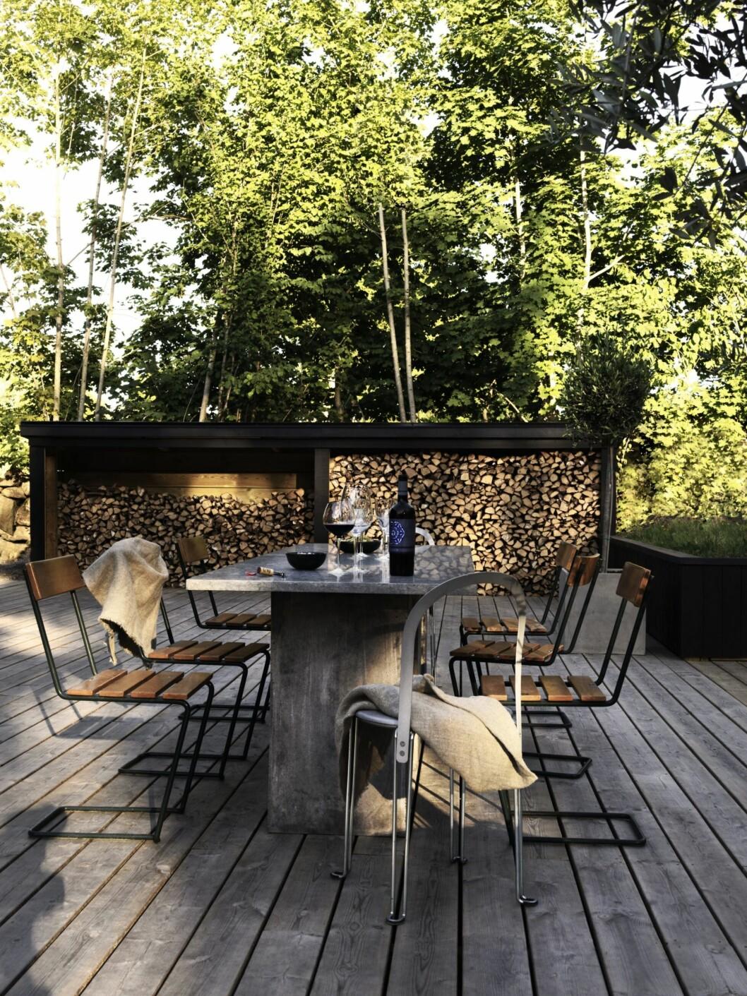 Uteplats i trä med både matbord och stolar i samma anda