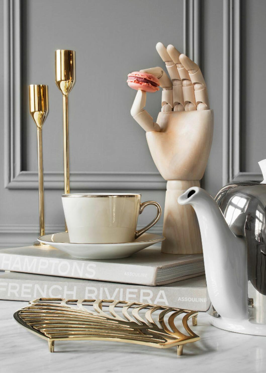 Stilleben på matbordet med ljusstakar, kopp och serveringsdetaljer