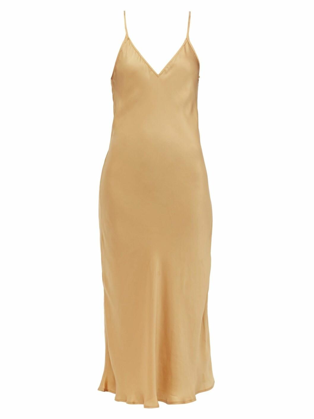 Slipklänning i beige med justerbara band och ett fint fall.