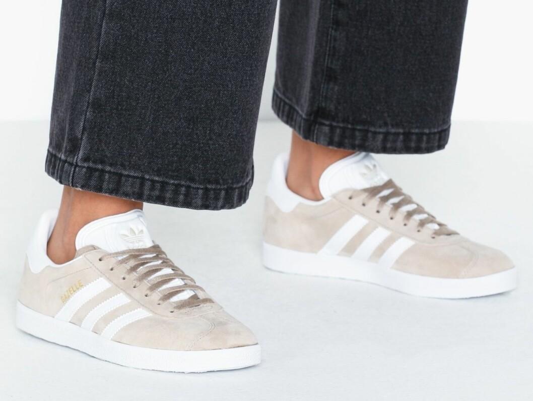 Sneakers i beige och detaljer i vitt från Adidas.