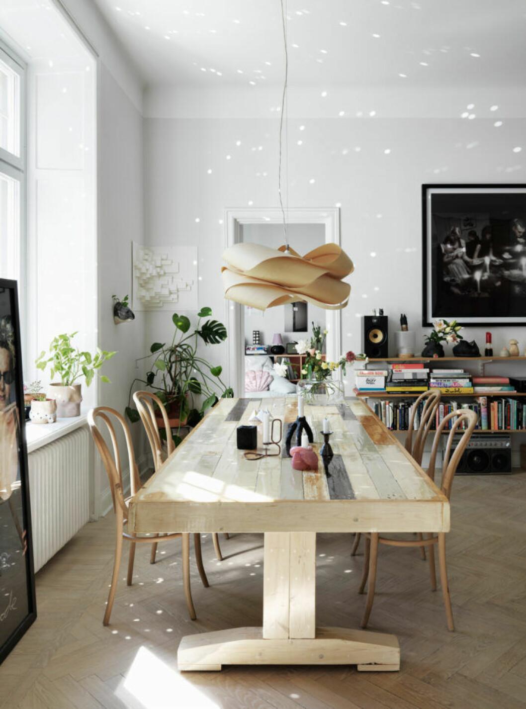 Matsalsbord, lampa och stolar i trä hos modedesignern på Södermalm i Stockholm