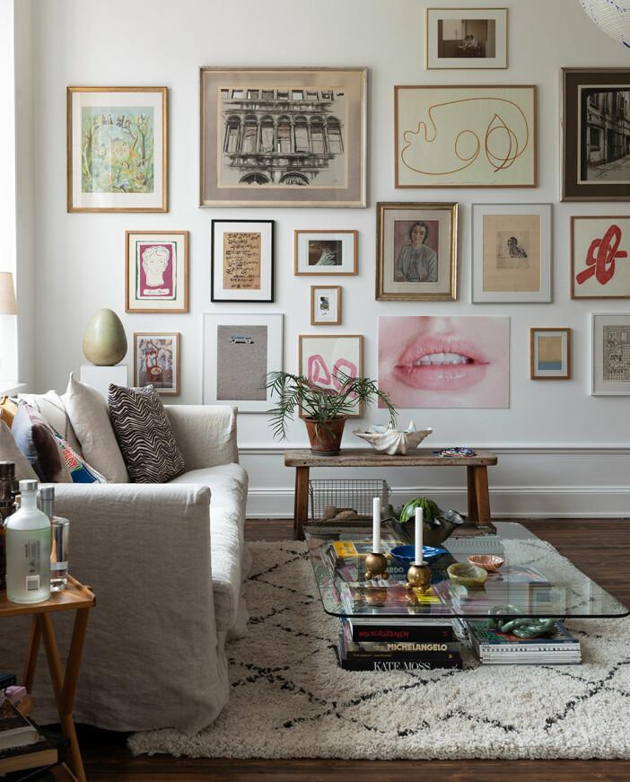 soffbord i glas med böcker och kreativ tavelvägg i bakgrunden