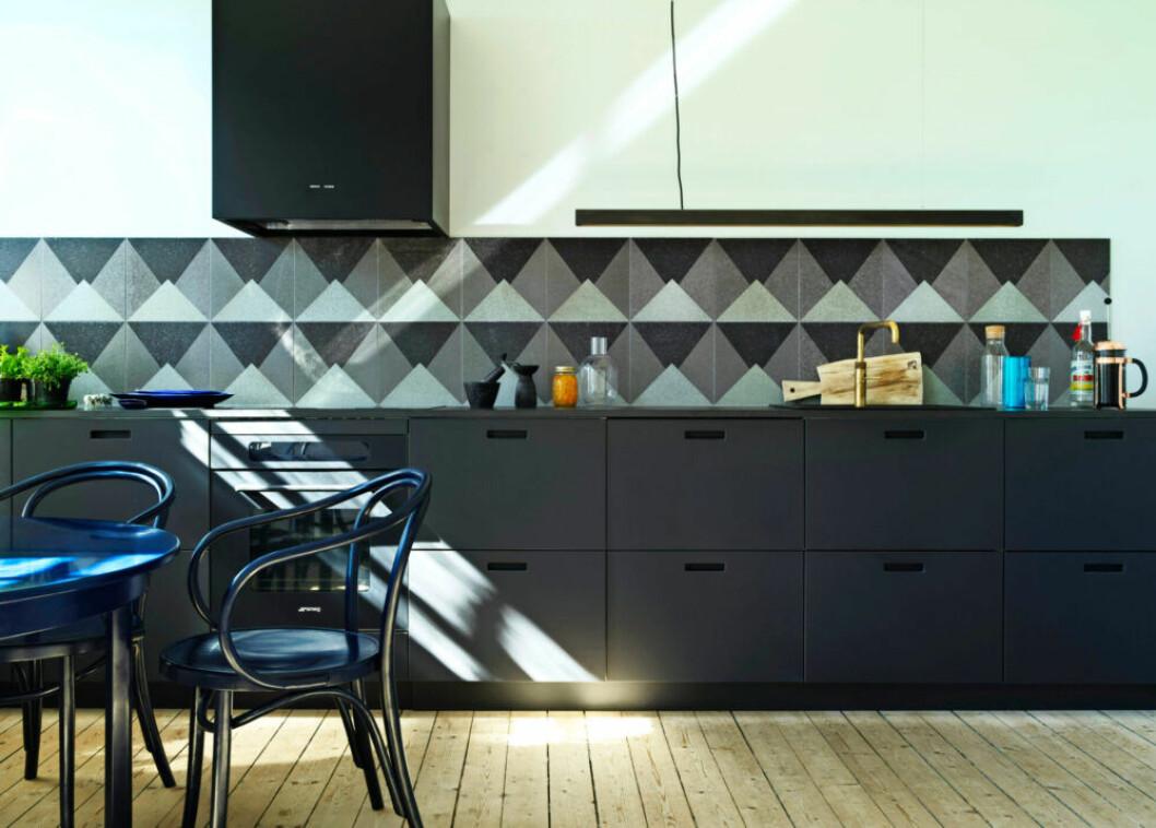 Köket går i svarta toner med kakel i olika nyanser av grått och svart