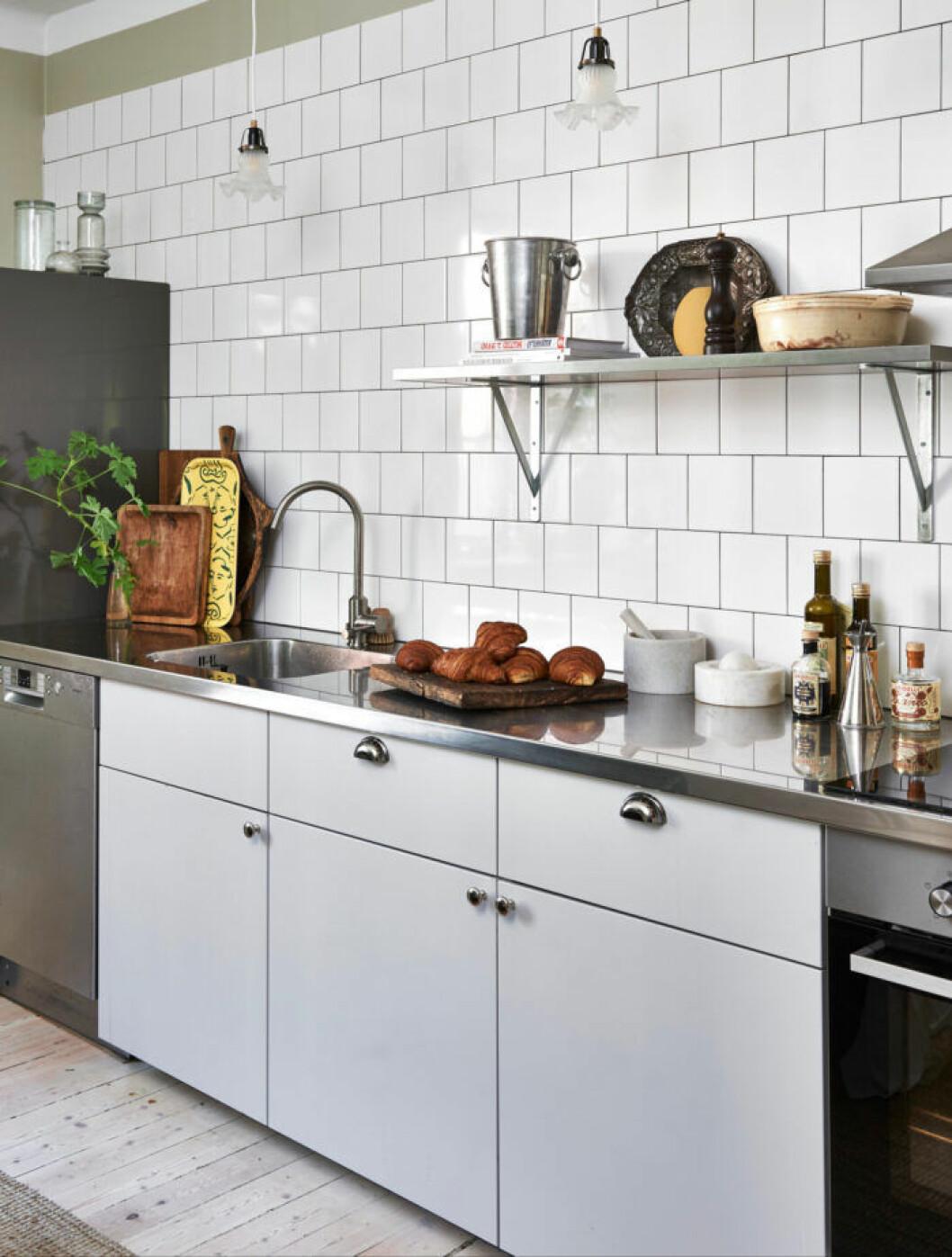 Stilrent kök i vitt och grått med vitt kakel