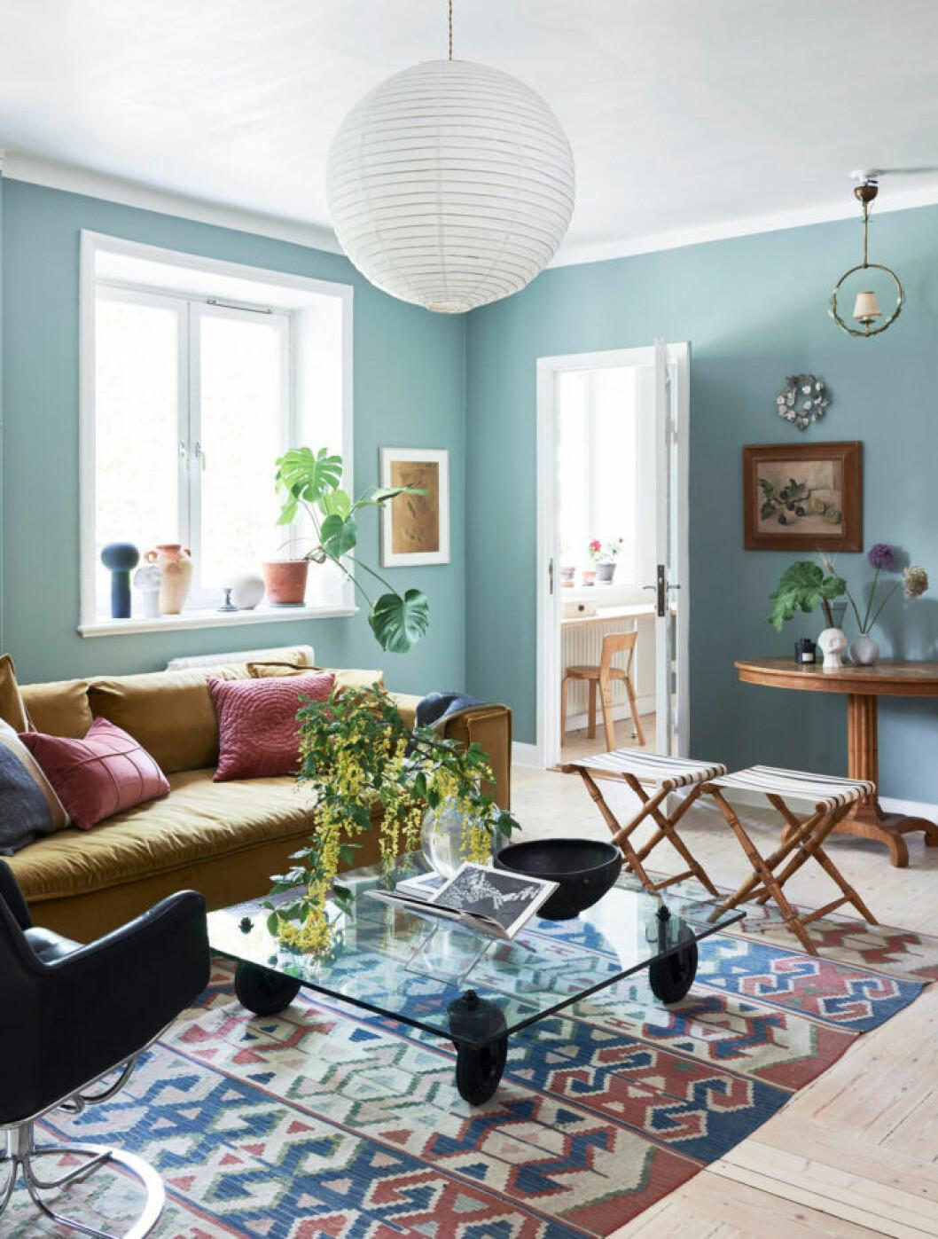 Vardagsrummet går i ljusblåa toner med detaljer i brunt, rosa och trä