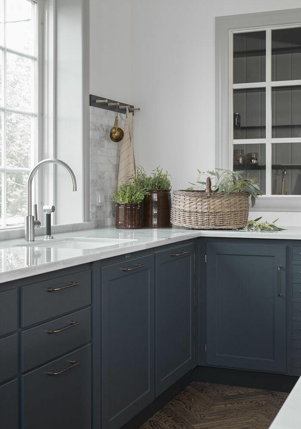 Kök med blå skåpsluckor från Kvänum med örter på köksbänken