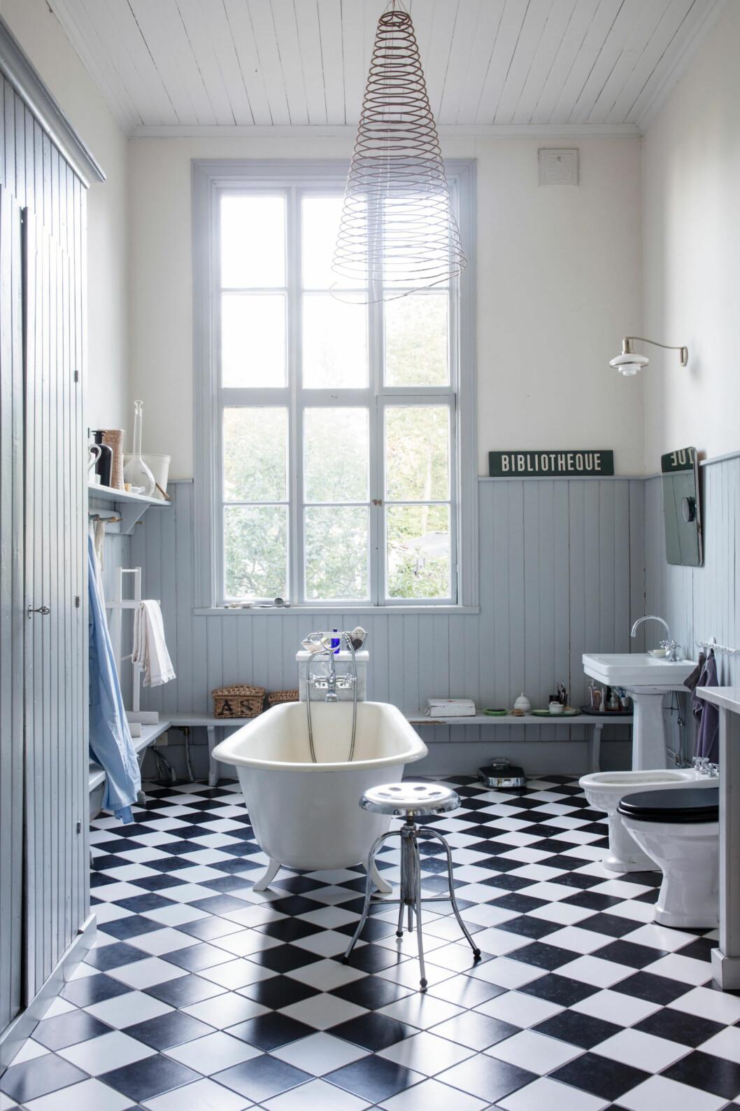 Badrummet har svartvitrutigt golv och väggar i vita och ljusblåa toner