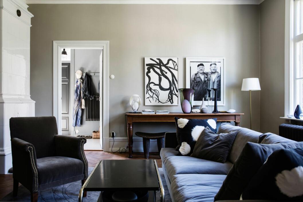 Vardagsrumsmöblerna går i mörka toner med inslag av sammet