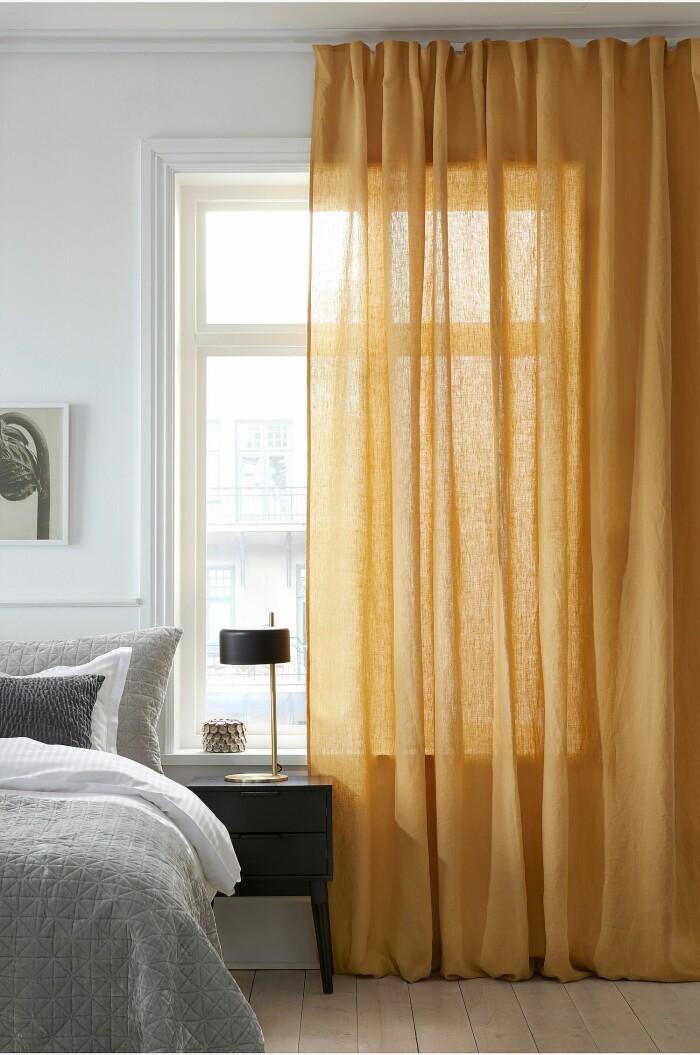 sovrum med gula gardiner och grå textilier