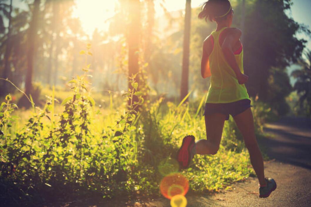 Kvinna springer i skogen på sommaren