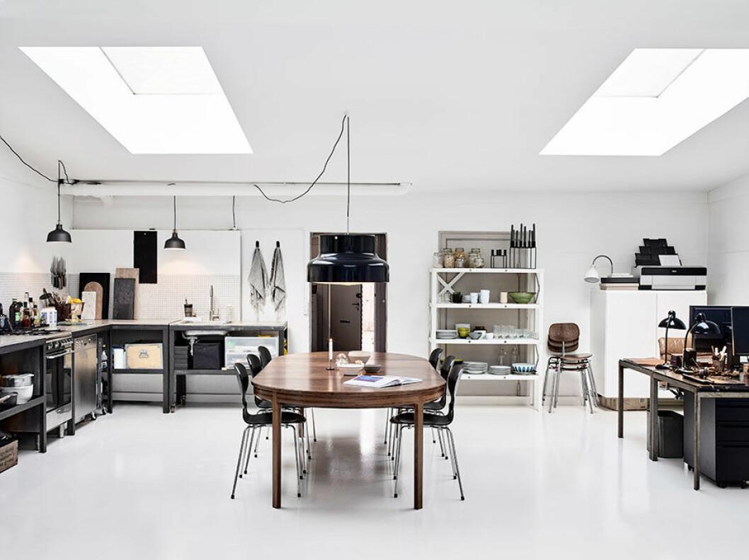 Allrummet om ca 70 kvadratmeter rymmer vardagsrum, kök, matplats och hemmakontor. De två gamla skrivborden av Poul Kjærholm köpte paret på en auktion på Arkitektskolan. Anders har själv byggt köket av öppna järnmoduler och rå betongskivor. Matbordet i teak är arvegods och måltiderna intas på svarta Myran-stolar av Arne Jacobsen. Svart Bumling från Ateljé Lyktan.
