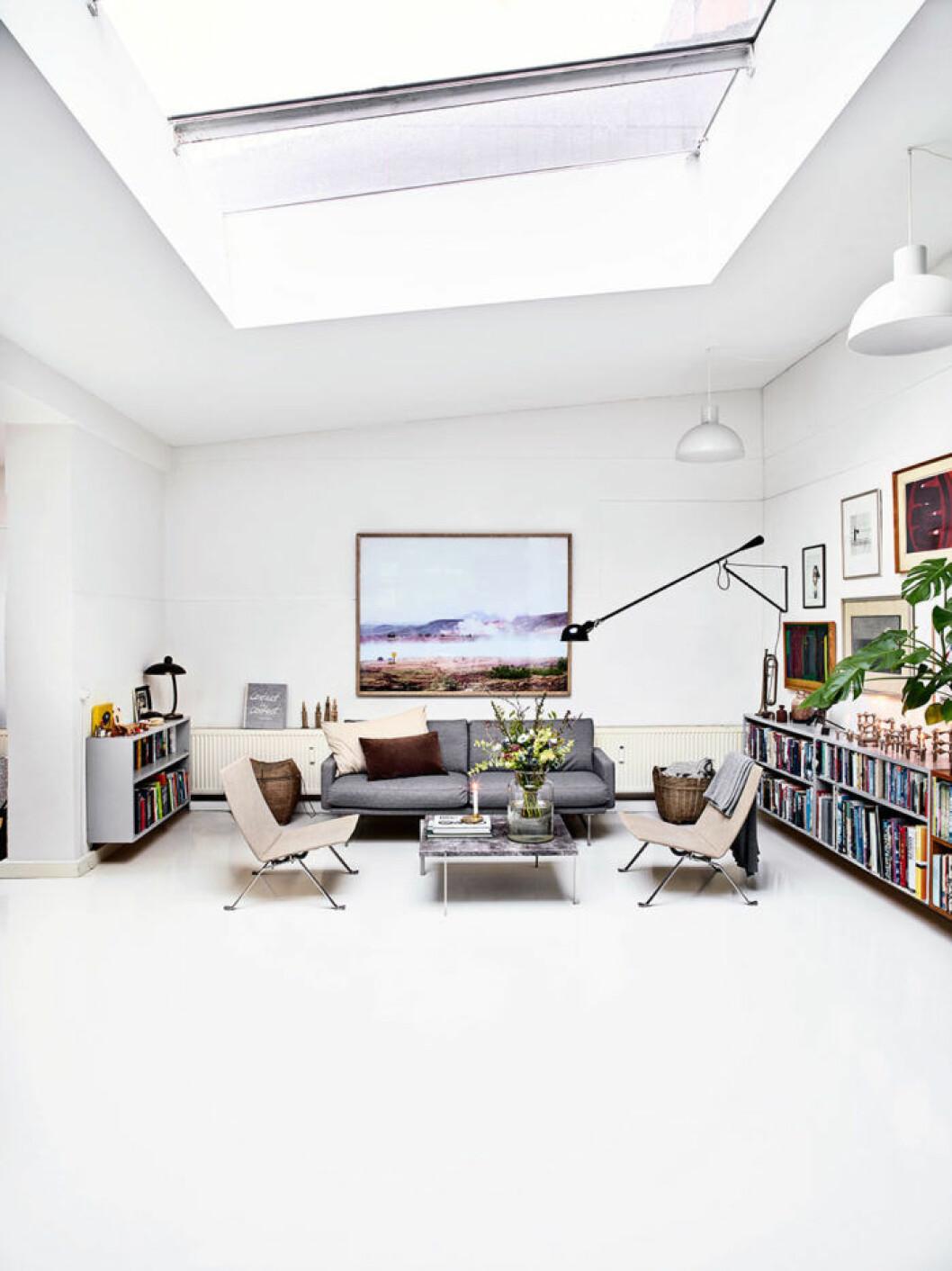 De stora takfönstren ger allrummet en nästan galleriaktig prägel. Ovan den grå Piero Lissoni-soffan hänger ett stort fotografi av Anders som togs under en semester på Island. Vägglampan 265, i design Paolo Rizzatto är med sitt industriella uttryck ett perfekt val till soffgruppen med PK22-stolar i canvas och PK61 soffbord i marmor, från Fritz Hansen.
