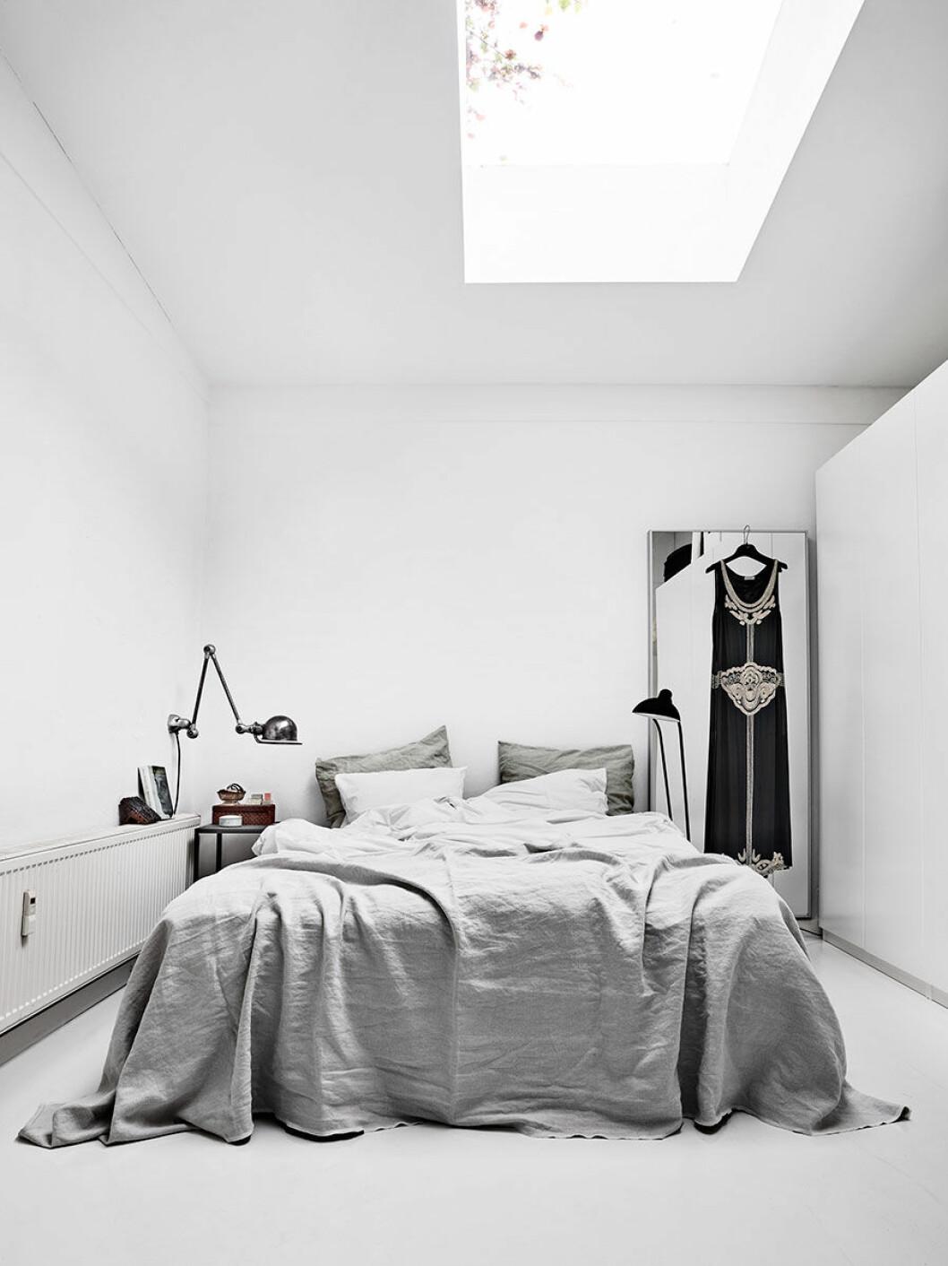 Från sängen  i det ljusa sovrummet  kan paret somna  till regnets trummande  på takfönstret.  Sängkläderna är  hemsydda av tyg från  belgiska Libeco.  Vintagelampa från  Jieldé och golvlampa  från Christian Dell.