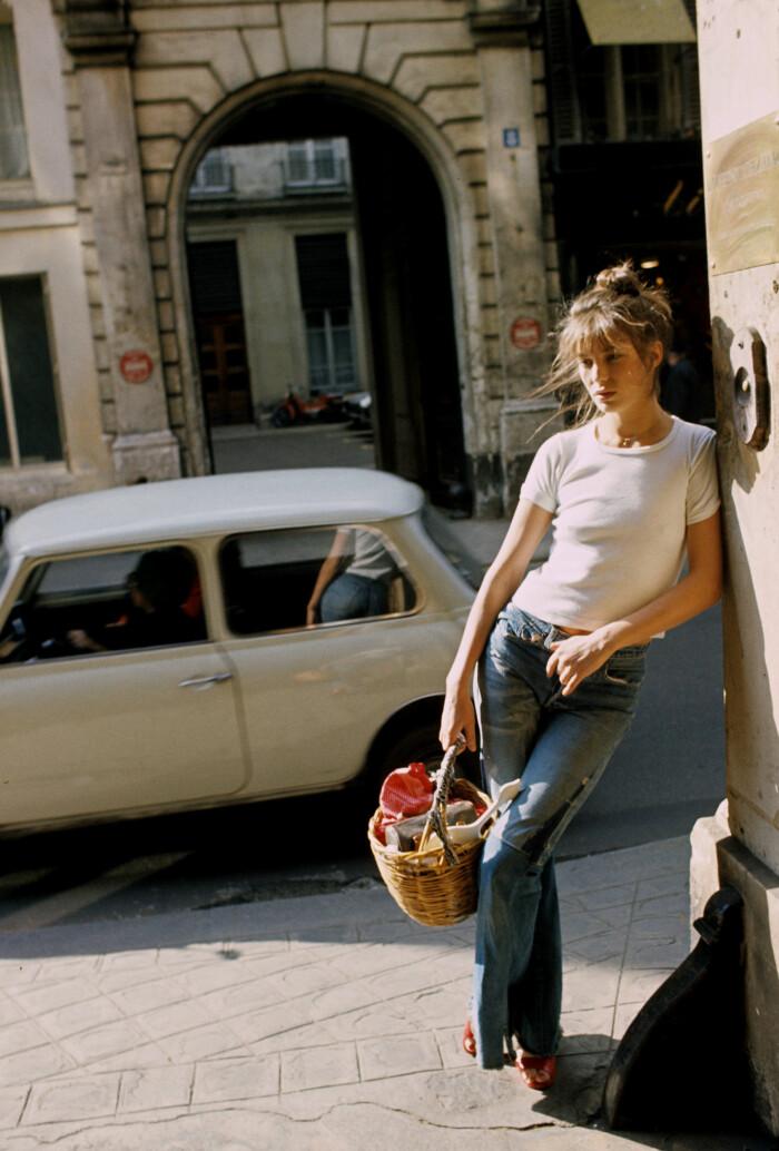 Stilikonen Jane Birkin år 1974 i vida jeans, enkel t-shirt och korgväska.