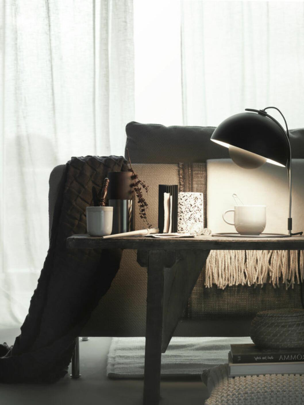 Soffa möblerad mot ett fönster och en dekorativ skänk bakom