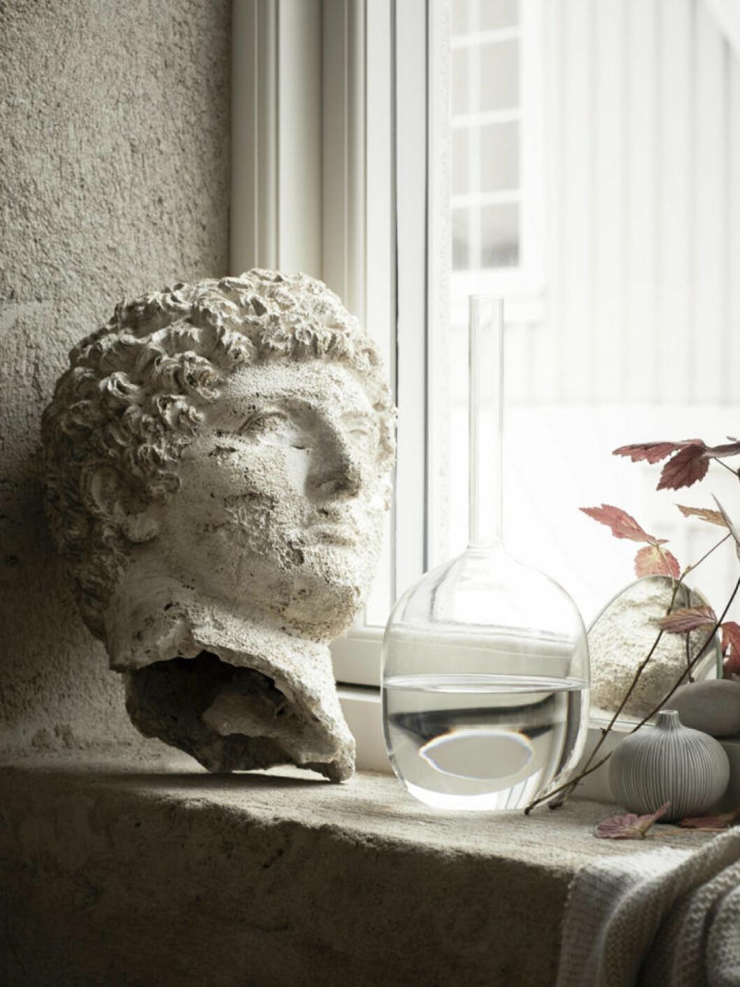 Skulptur av ansikte samt glasvas i ett fönster