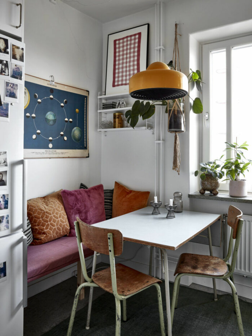 Mysig matplats i köket med färgglada textilier, orange lampa och trästolar