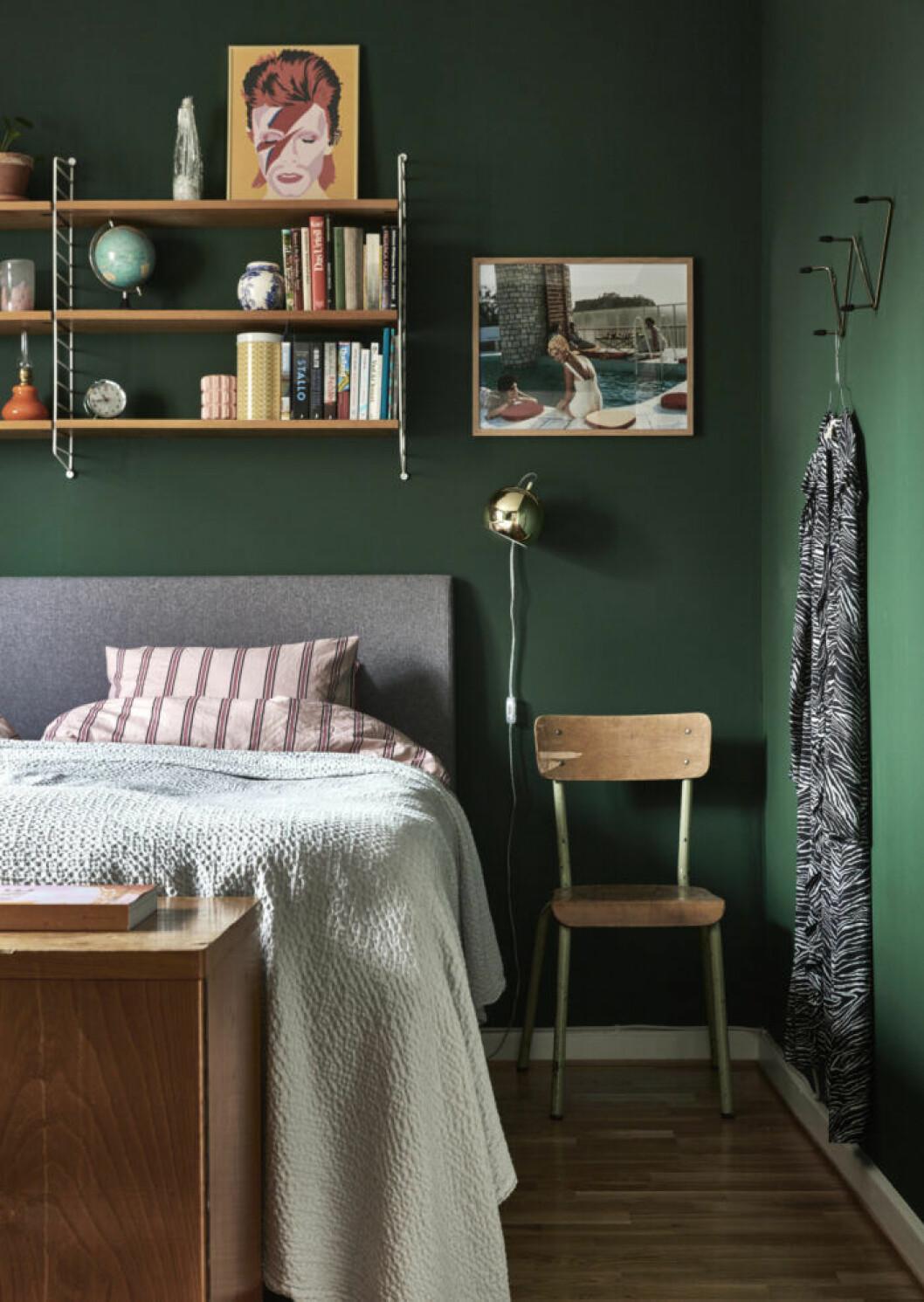 Det mörkgrönmålade sovrummet med väggfäst bokhylla