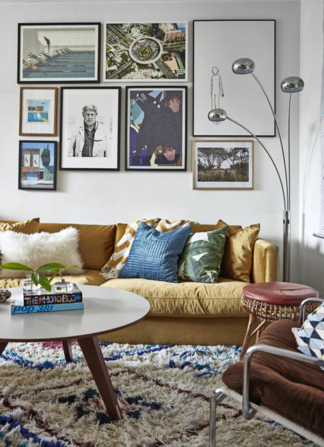 Tavelvägg, gul soffa och metallisk golvlampa i vardagsrummet