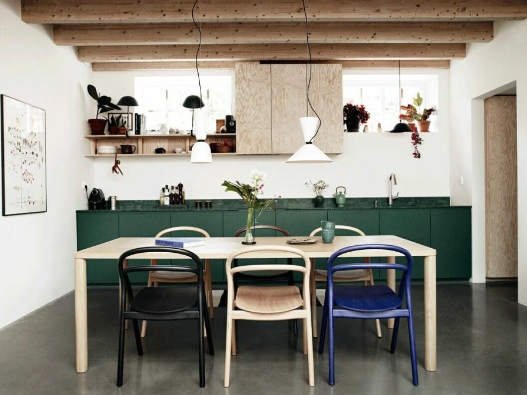 Kök, stolar i olika färger, gröna köksluckor