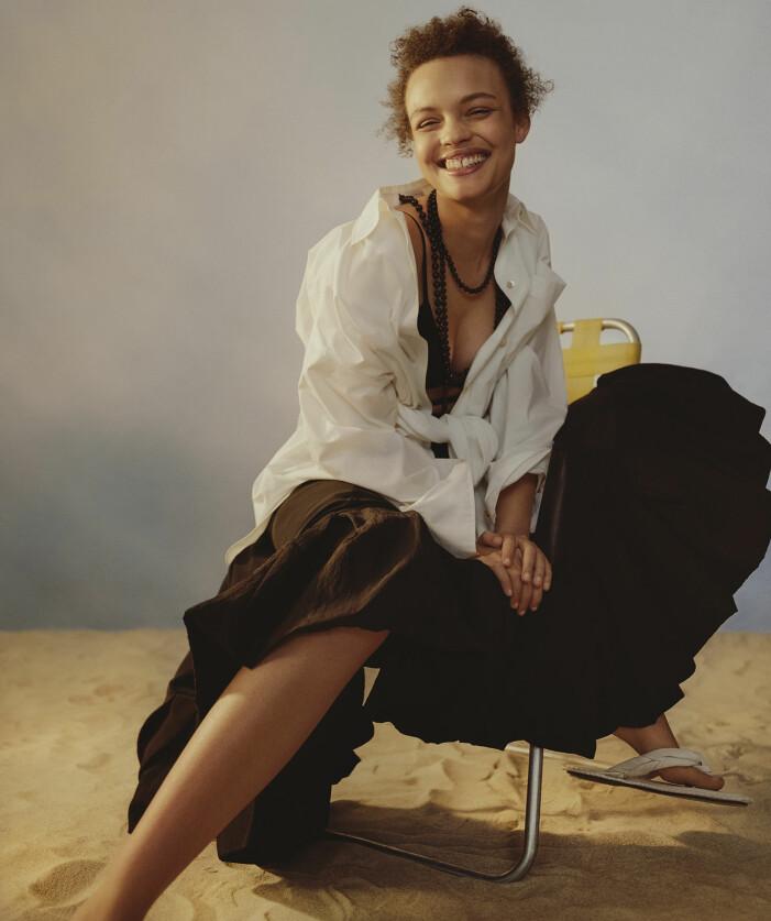 Modellen har på sig en vit skjorta och brun kjol från Rejina Pyo