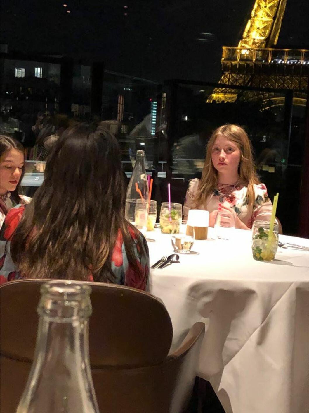 Tre tjejer sitt rrunt ett middagsbord och väntar på maten