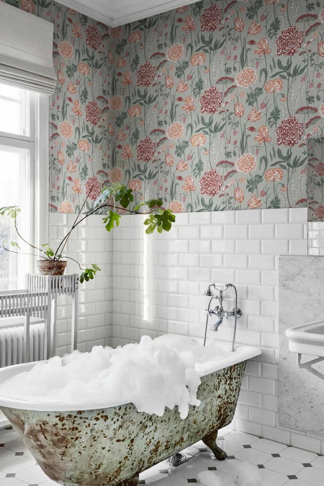 Blommig tapet i badrum med halvkaklat och badkar