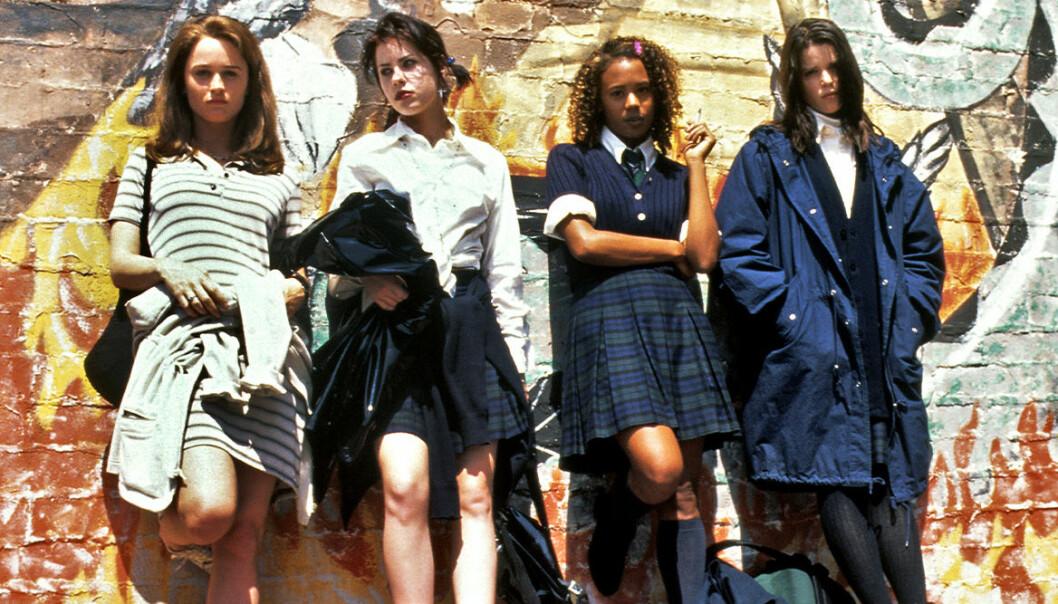 Tjejerna från kultfilmen The Craft 1996 uppradade mot en vägg i coola 90-tals kläder.