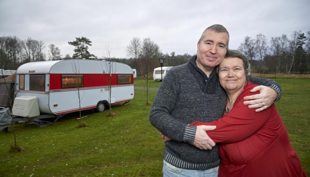 Thomas och Carina står framför sin husvagn, håller om varandra och berättar om hur det kom sig att de valde att bo permanent i en husvagn.