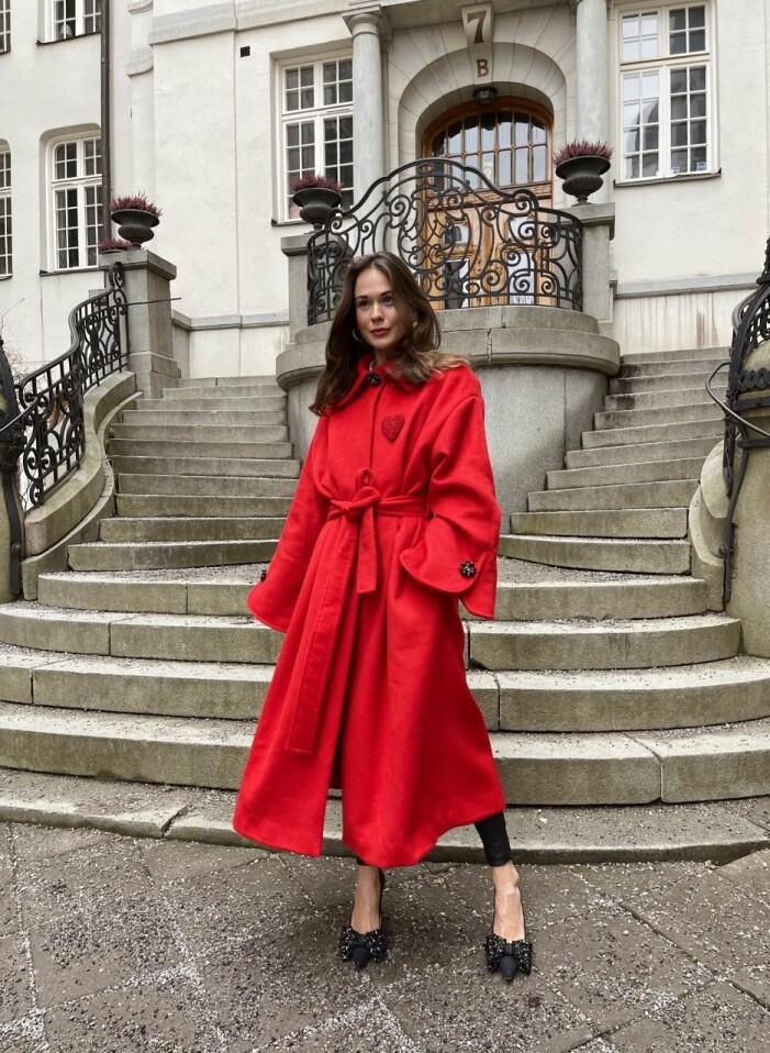 Therese Hellström i en röd kappa och svarta högklackade skor.