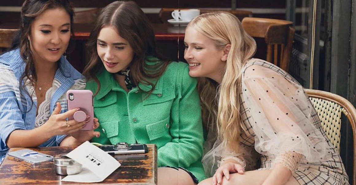 Emily in Paris och två vänner tittar på en mobiltelefon