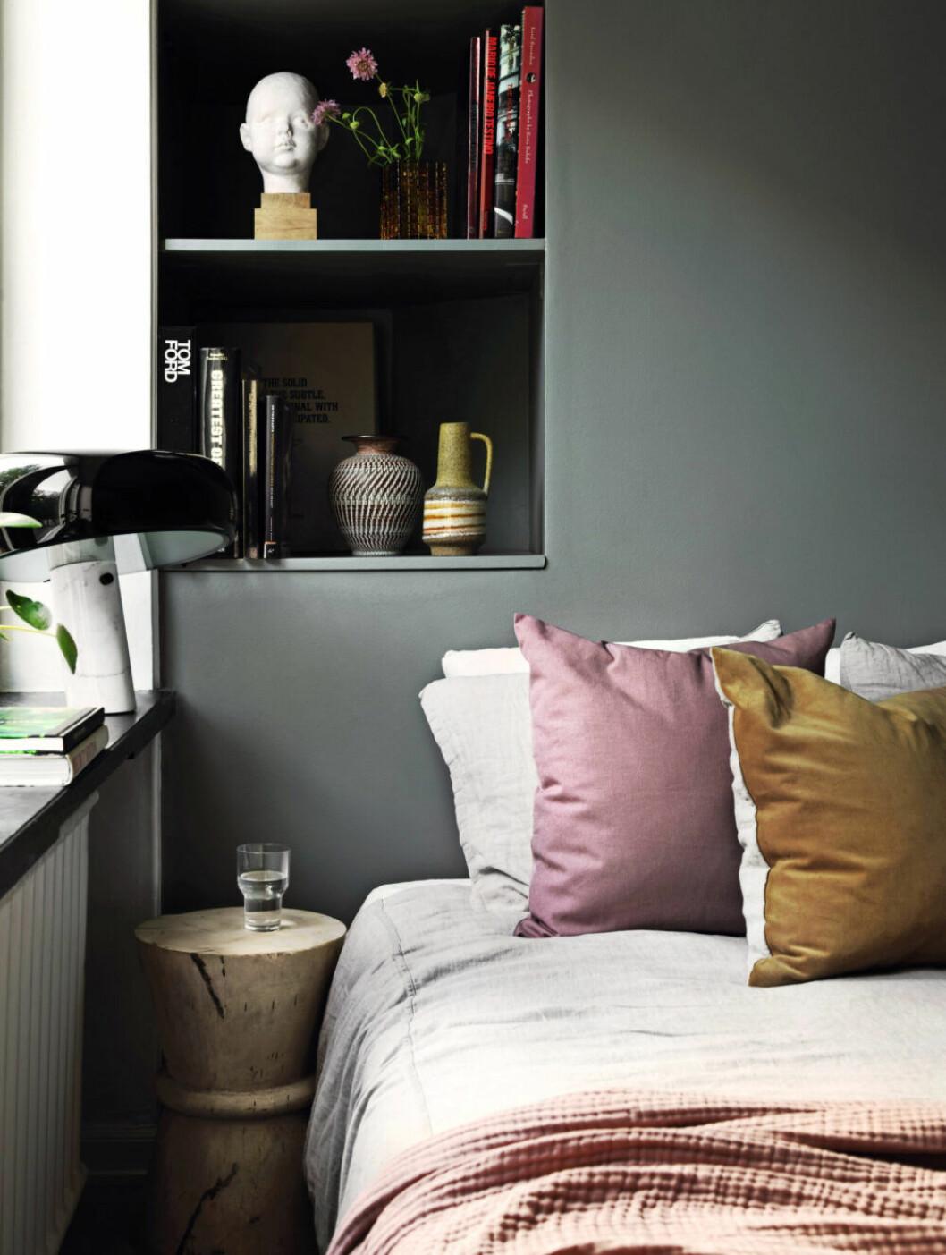 Pastellfärgade kuddar bryter den gråa färgen på väggen i sovrummet