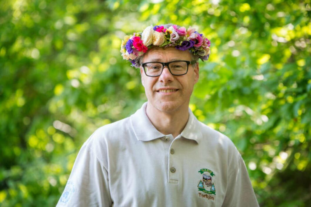 Torbjörn Johannesson står med blomsterkrans i håret och tittar in i kameran och ler