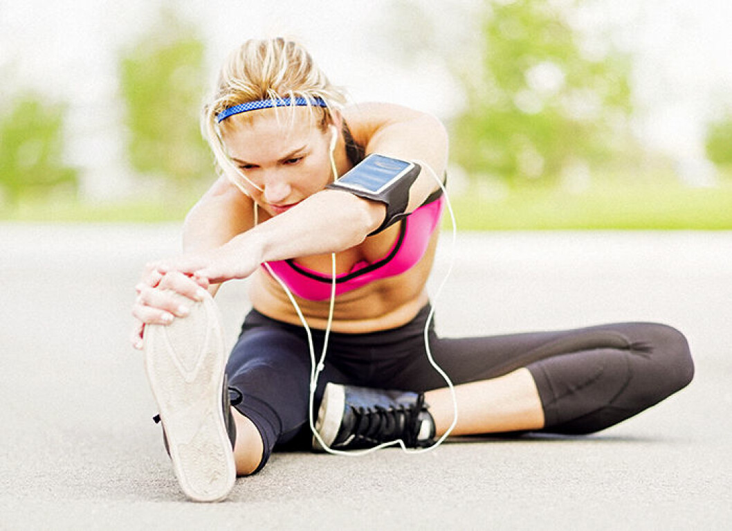 Young woman listening to music while stretching
