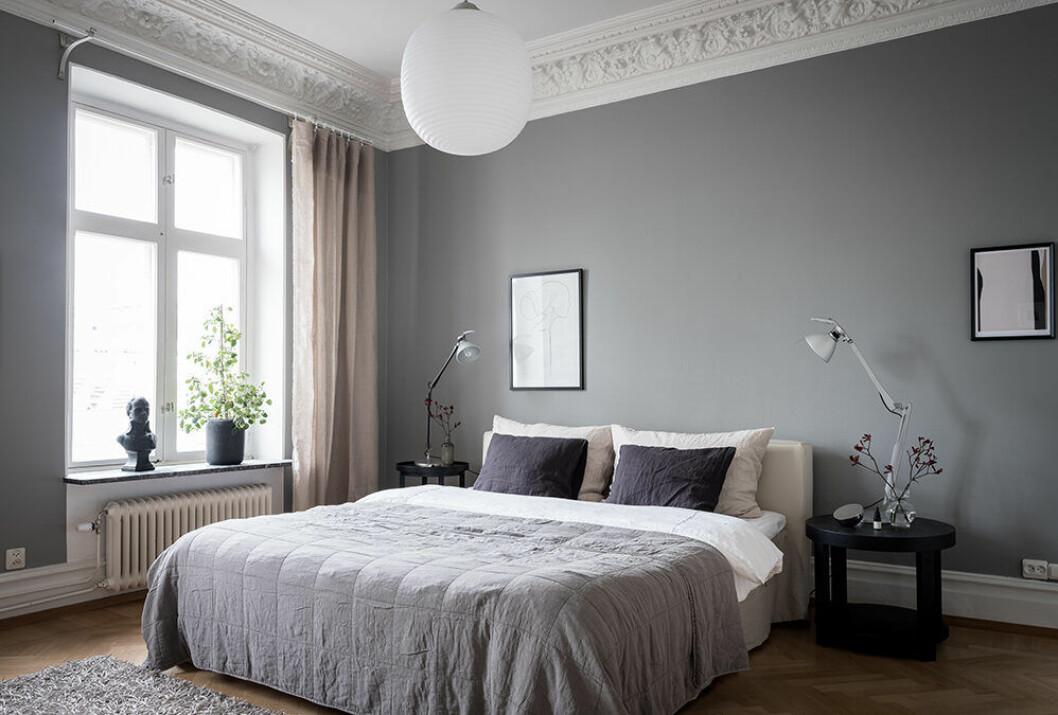 Sovrum med trendig bäddning i hotellstil med överkast i grått