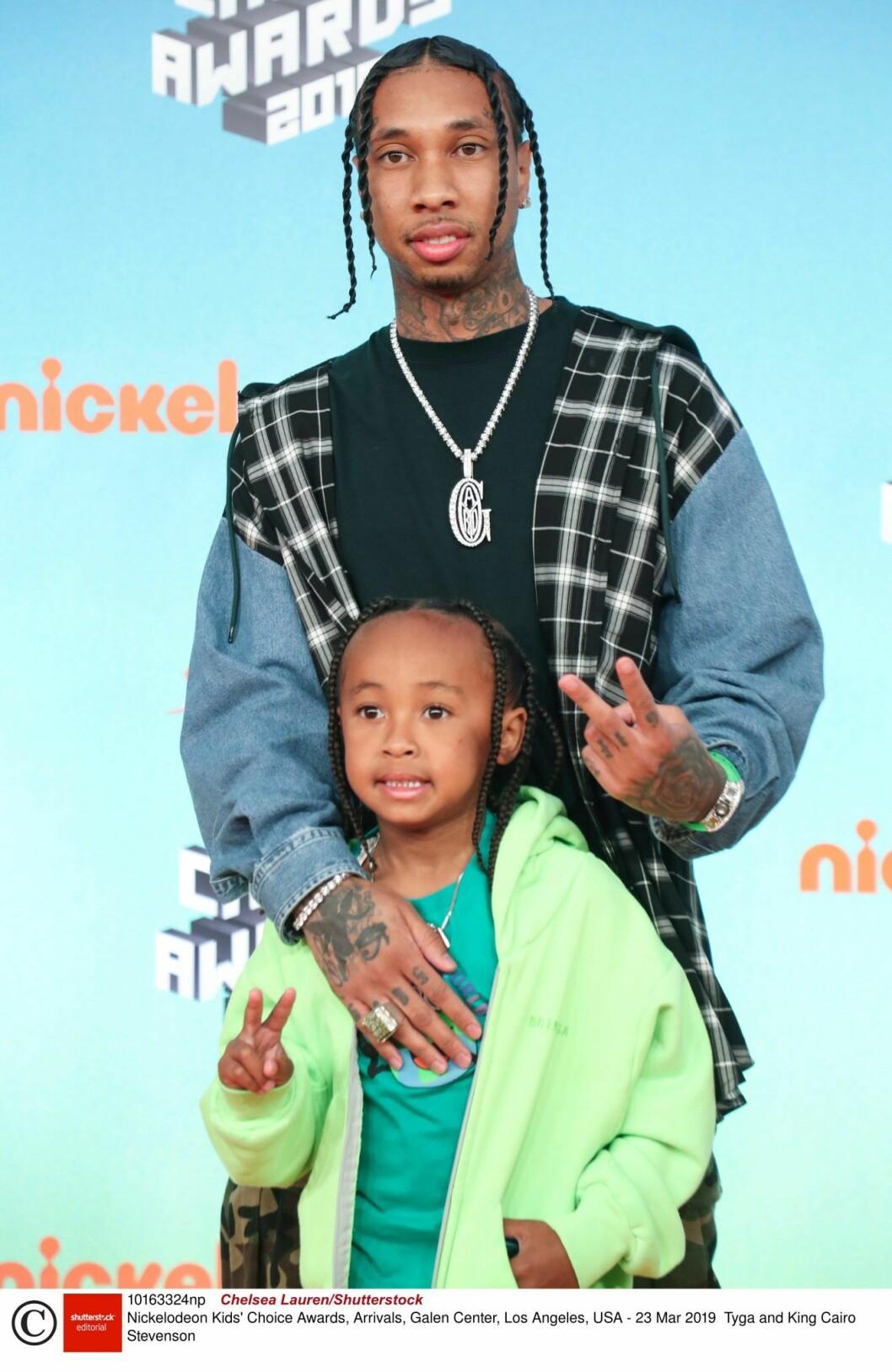 Tyga står bakom sonen King och håller om honom och de båda gör v-tecken med fingrarna