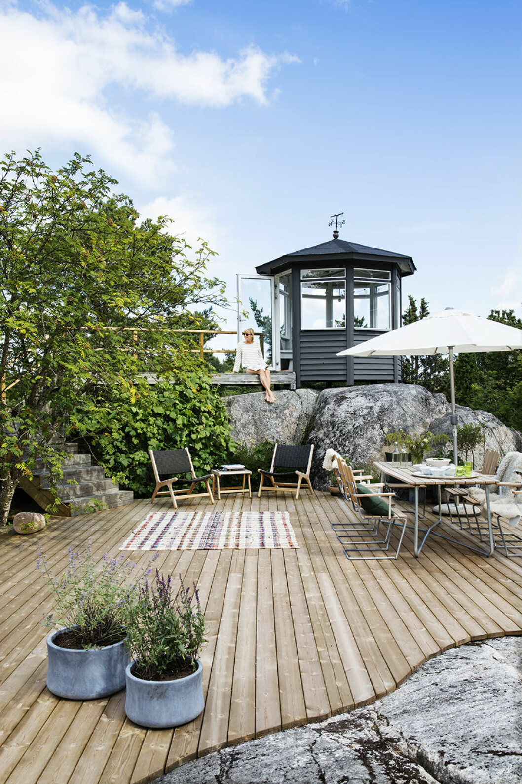Uteplats i skärgården med platsbyggt trädäck mellan bergen