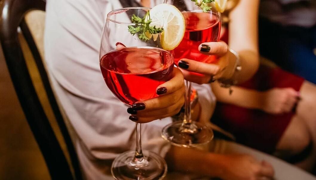 Två kvinnor med nagellack håller i röda drinkar.