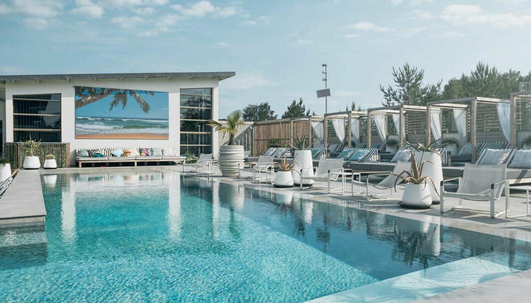 En pool med turkost vatten och cabanas runt omkring