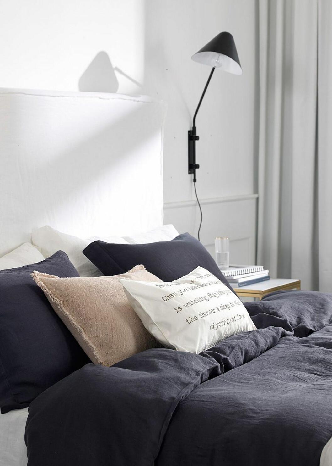 Sovrum med vägghängd svart lampa