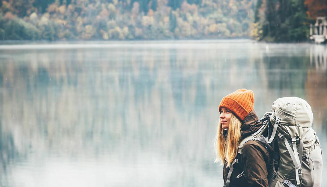 Kvinna vandrar i skog vid en sjö.