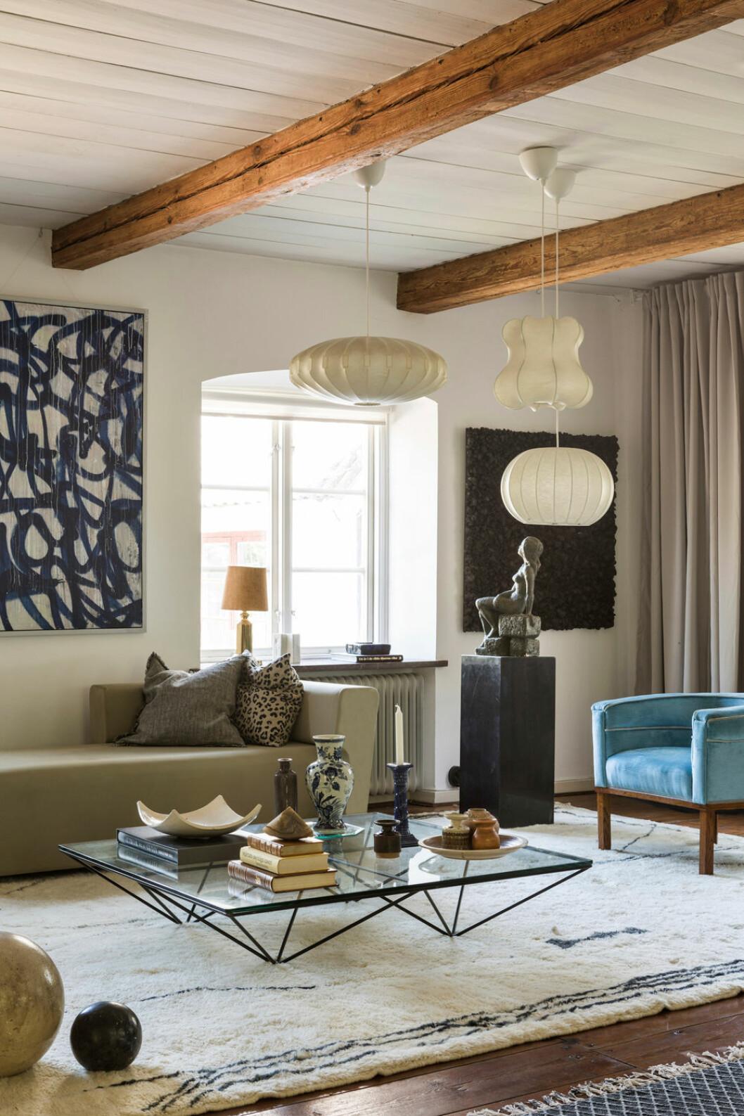 Hemma hos Fredrika Artndeco vardagsrum blå fåtölj lampor