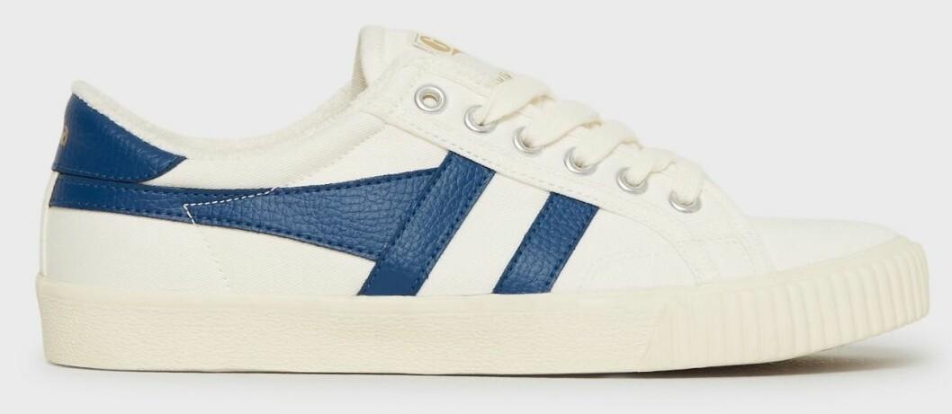 Sneakers med detaljer i blått och vitt som gör sig fin tillsammans med mörkblå jeans.