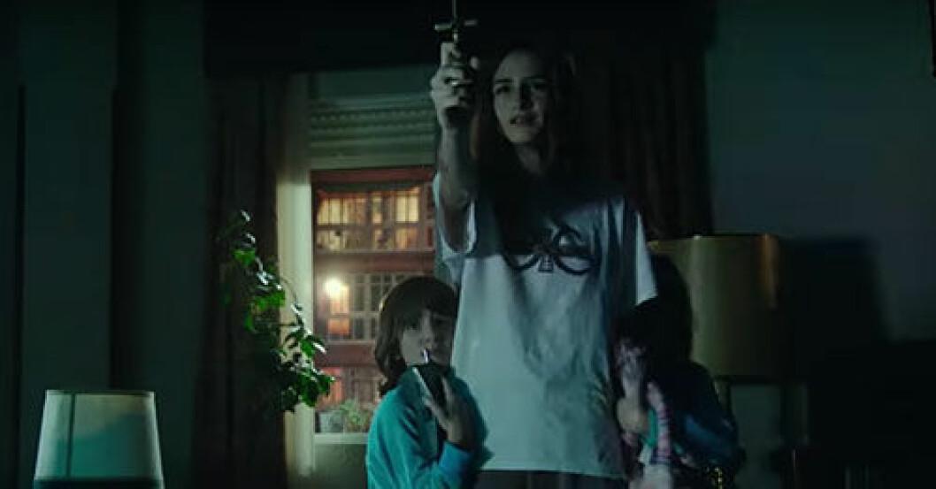 Veronica håller upp ett kors för att skydda sig själv och sin lillebror mot onda andar i skräckfilmen Veronica som finns på Netflix.