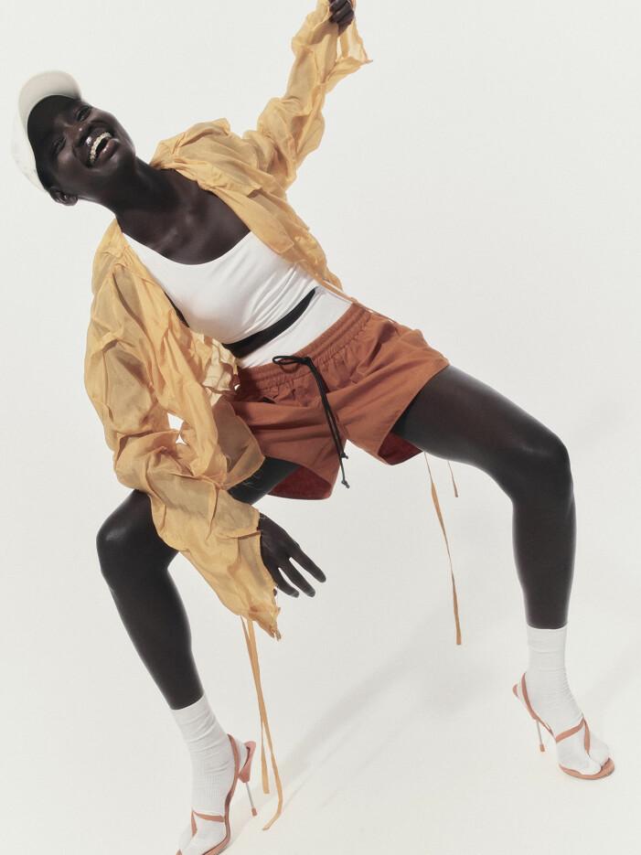 Modellen har på sig en vit baddräkt, gul blus och orange shorts