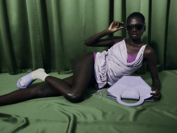 Modellen har på sig lila klänning, baddräkt och skor