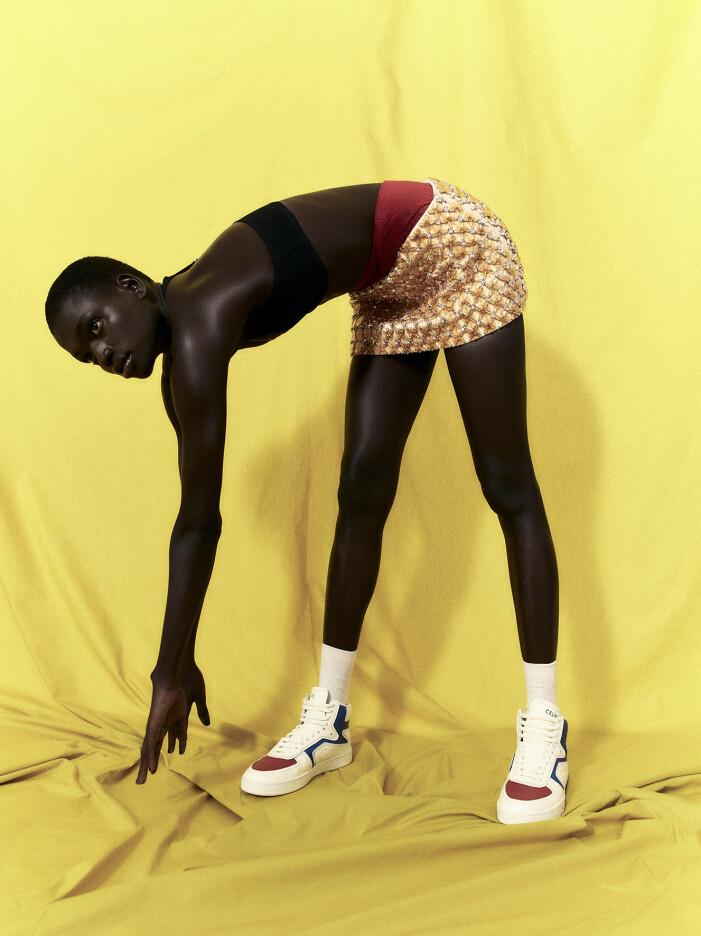 Modellen har på sig en svart bikinitopp, röda shorts och en guldig kjol