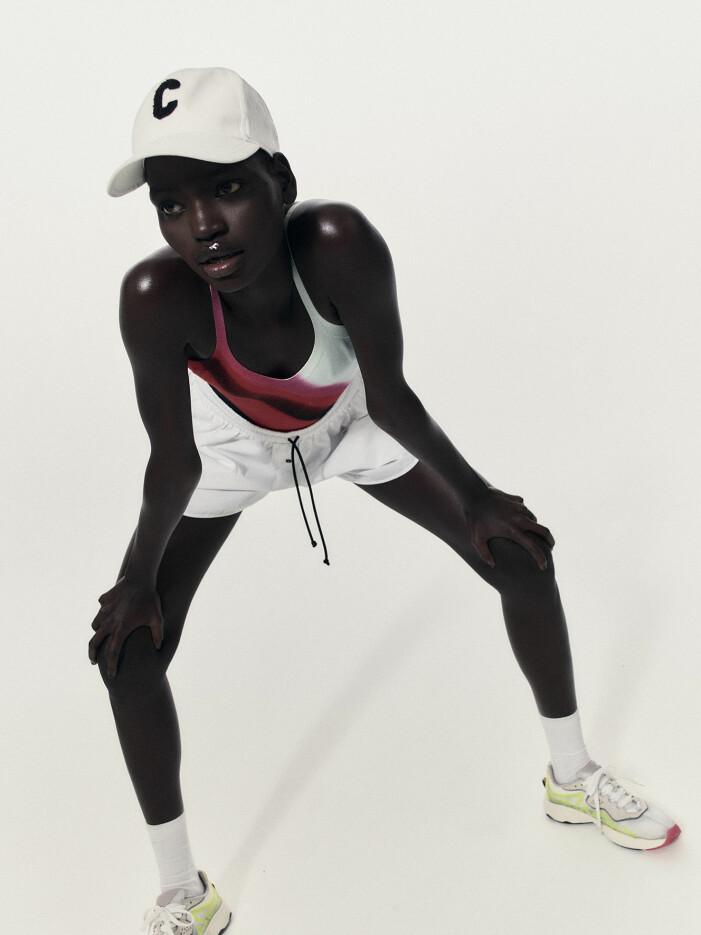 Modellen bär en mönstrad baddräkt, vita shorts och sneakers