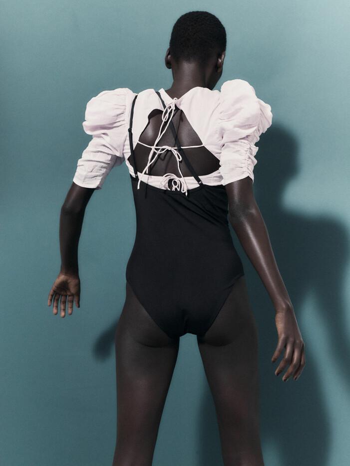 Modellen har på sig en svart baddräkt och en vit blus