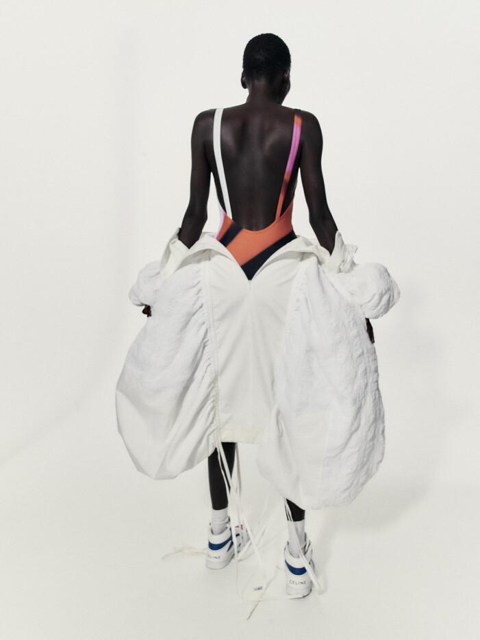 Modellen bär en mönstrad baddräkt, vit klänning och sneakers